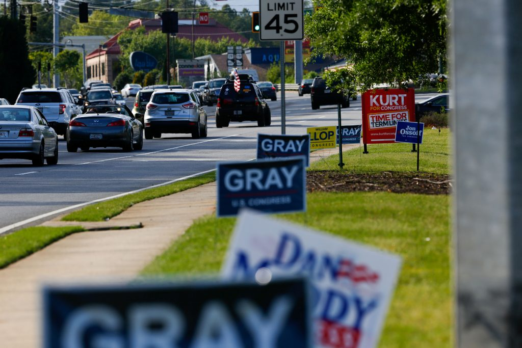 Campaign signs for candidates for Georgia's 6th Congressional District special election, which will fill the seat vacated when Republican Tom Price was appointed as secretary of Health and Human Services, line Holcomb Bridge Road in Alpharetta, Georgia, U.S. April 17, 2017. Picture taken April 17, 2017. REUTERS/Kevin D. Liles - RTS12SM2