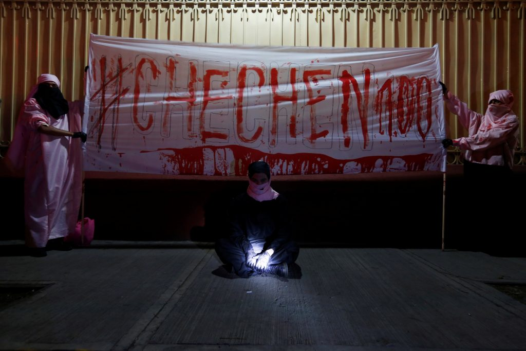 Activists from the group Chok3 stand next to a banner painted with their own blood during a protest against the constant discrimination and violence against the gay community in Chechnya and other regions of Russia, outside the Russian embassy in Mexico City, Mexico. Photo by Carlos Jasso/Reuters