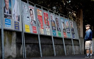 A man looks at campaign posters of the 11th candidates who are running in the 2017 French presidential election in Enghien-les-Bains, near Paris, on April 19. Photo by Christian Hartmann/Reuters