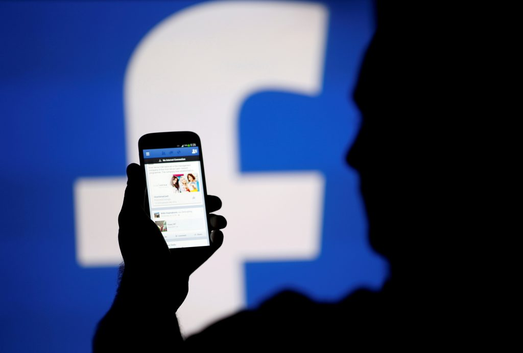 FILE PHOTO: A man is silhouetted against a video screen with a Facebook logo as he poses with a Samsung S4 smartphone in this photo illustration August 14, 2013. REUTERS/Dado Ruvic/File Photo - RTS13XE0