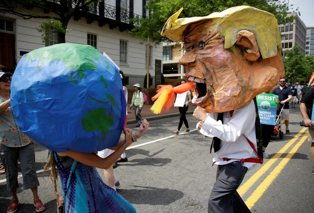 Protesters dressed as the earth and U.S. President Donald Trump pretend to fight during the Peoples Climate March near the White House in Washington