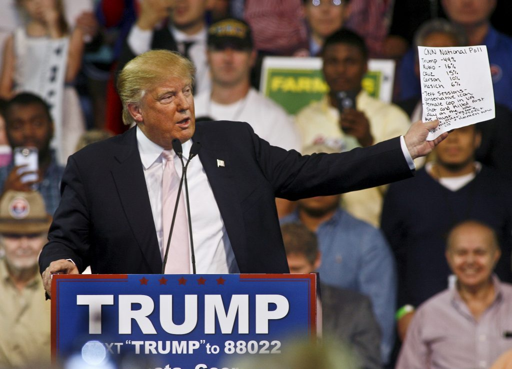 Republican U.S. presidential candidate Donald Trump holds up a CNN national poll showing him with a commanding lead as he speaks at a campaign rally at Valdosta State University in Valdosta, Georgia February 29, 2016. REUTERS/Philip Sears - RTS8OC0