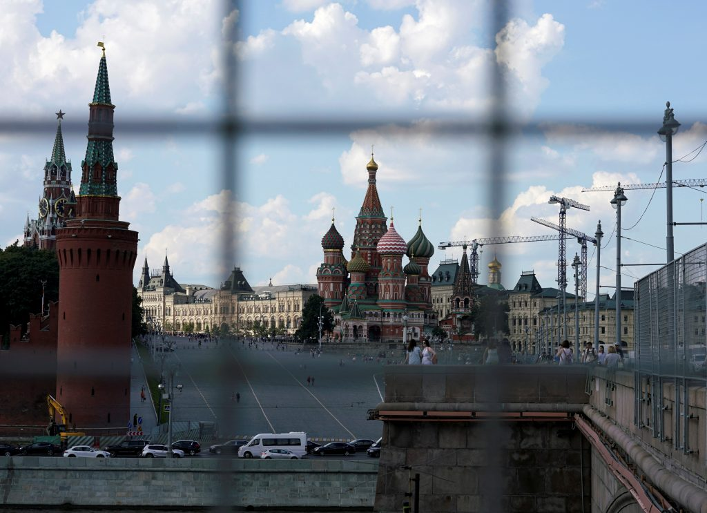 A view through a construction fence shows the Kremlin towers and St. Basil's Cathedral on a hot summer day in central Moscow, Russia, July 1, 2016. REUTERS/Maxim Zmeyev/File Photo - RTSK9HC