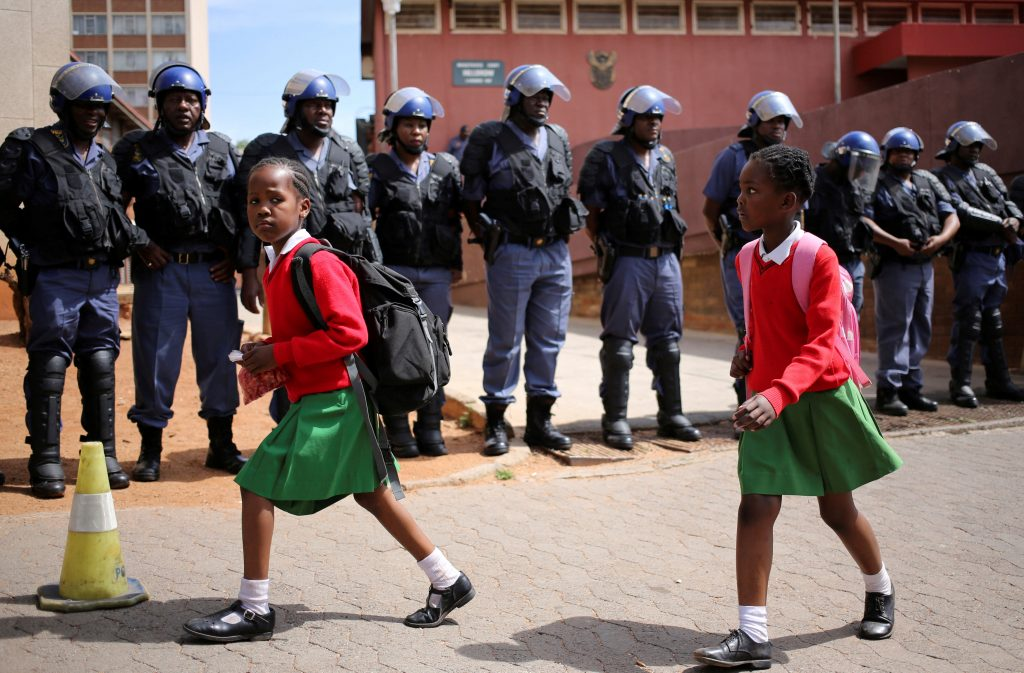 School girls walk past riot police standing guard outside Hillbrow magistrate court during an appearance of students who were arrested during a protest demanding free education at the Johannesburg's University of the Witwatersrand, South Africa. Photo taken in October 2016. Photo by Siphiwe Sibeko/Reuters