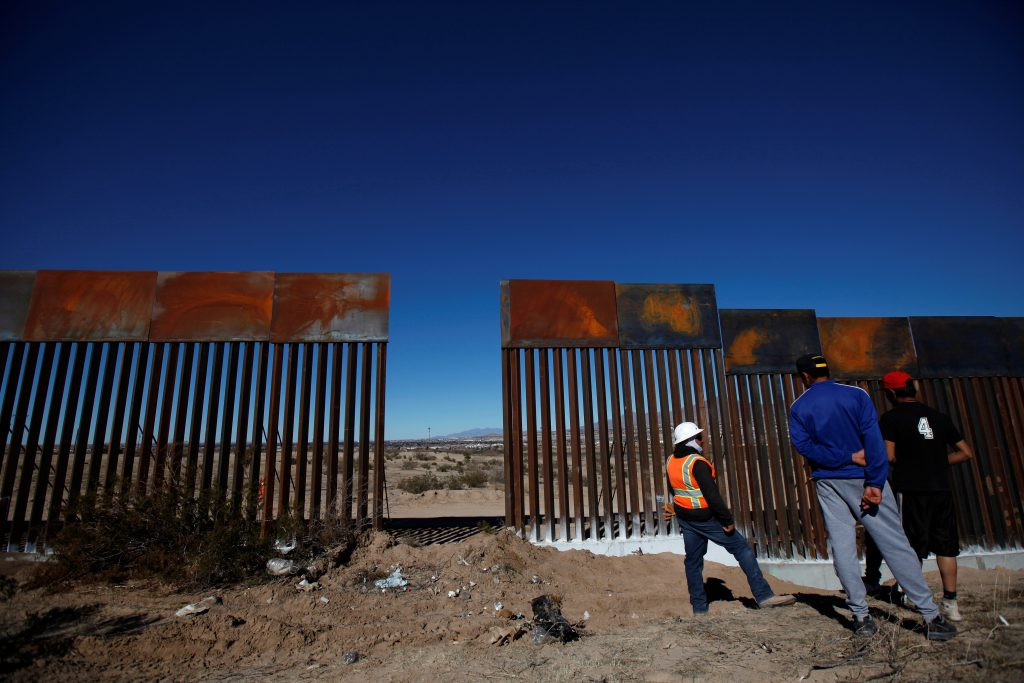 A worker chats with residents at a newly built section of the U.S.-Mexico border fence at Sunland Park, U.S. opposite the ...