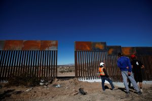 A worker chats with residents at a newly built section of the U.S.-Mexico border fence at Sunland Park, U.S. opposite the Mexican border city of Ciudad Juarez, Mexico. Photo taken in January. Photo by Jose Luis Gonzalez/Reuters