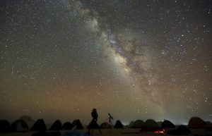 The 'Milky Way' is seen in the night sky around telescopes and camps of people over rocks in the White Desert north of the Farafra Oasis southwest of Cairo May 16, 2015. The White Desert, about 500 km southwest of the Egyptian capital Cairo, features limestone and chalk forms strangely shaped by the wind and sand, a terrain that gains in intensity when illuminated by the moon. Slightly to the north lies the Black Desert, given its name by the volcanic rock dolerite, similar to basalt. Four-by-four and trekking trips for tourists include Bedouin music around campfires and nights slept under a breathtaking array of stars. Picture taken May 16, 2015. REUTERS/Amr Abdallah Dalsh - RTX1FD3S