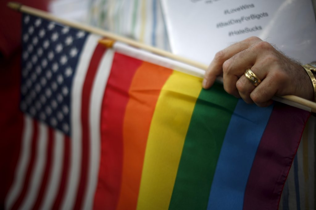 A married gay man carries the rainbow and U.S. flags at a celebration rally in West Hollywood, California, following the 2015 Supreme Court decision on marriage equality. Photo by Nicholson/Reuters
