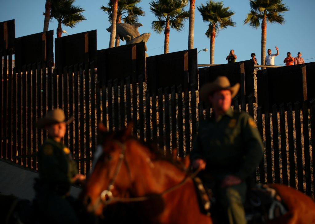 People in Mexico wave at U.S. Border Patrol agents on horseback patrolling the U.S.-Mexico border fence near San Diego, California, in 2016. Photo by Mike Blake/Reuters