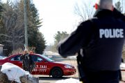 A man who says he is from Bangladesh, is confronted by a Royal Canadian Mounted Police (RCMP) officer as he exits a taxi at the U.S.-Canada border leading into Hemmingford, Quebec, Canada