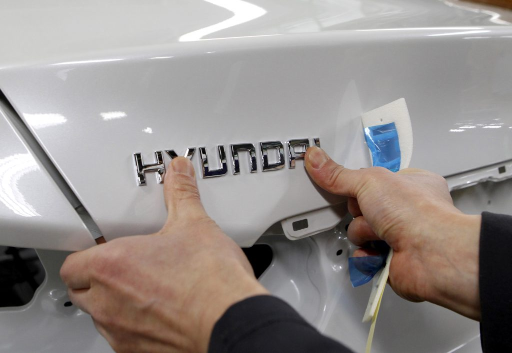 FILE PHOTO: A worker fixes the Hyundai logo on a vehicle at a plant of Hyundai Motor in Asan, south of Seoul