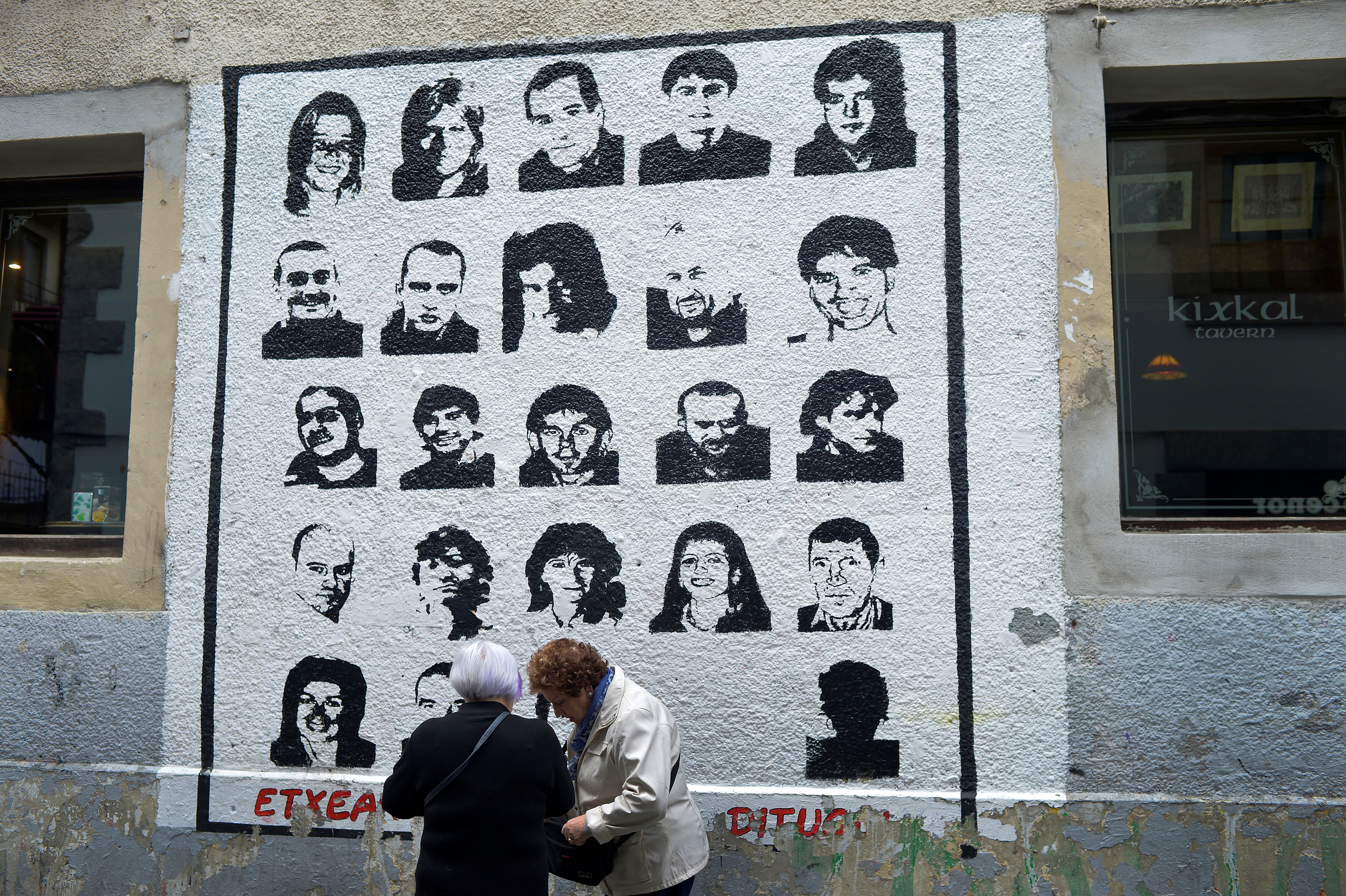 Women speak alongside a mural depicting imprisoned armed Basque group ETA members in Hernani