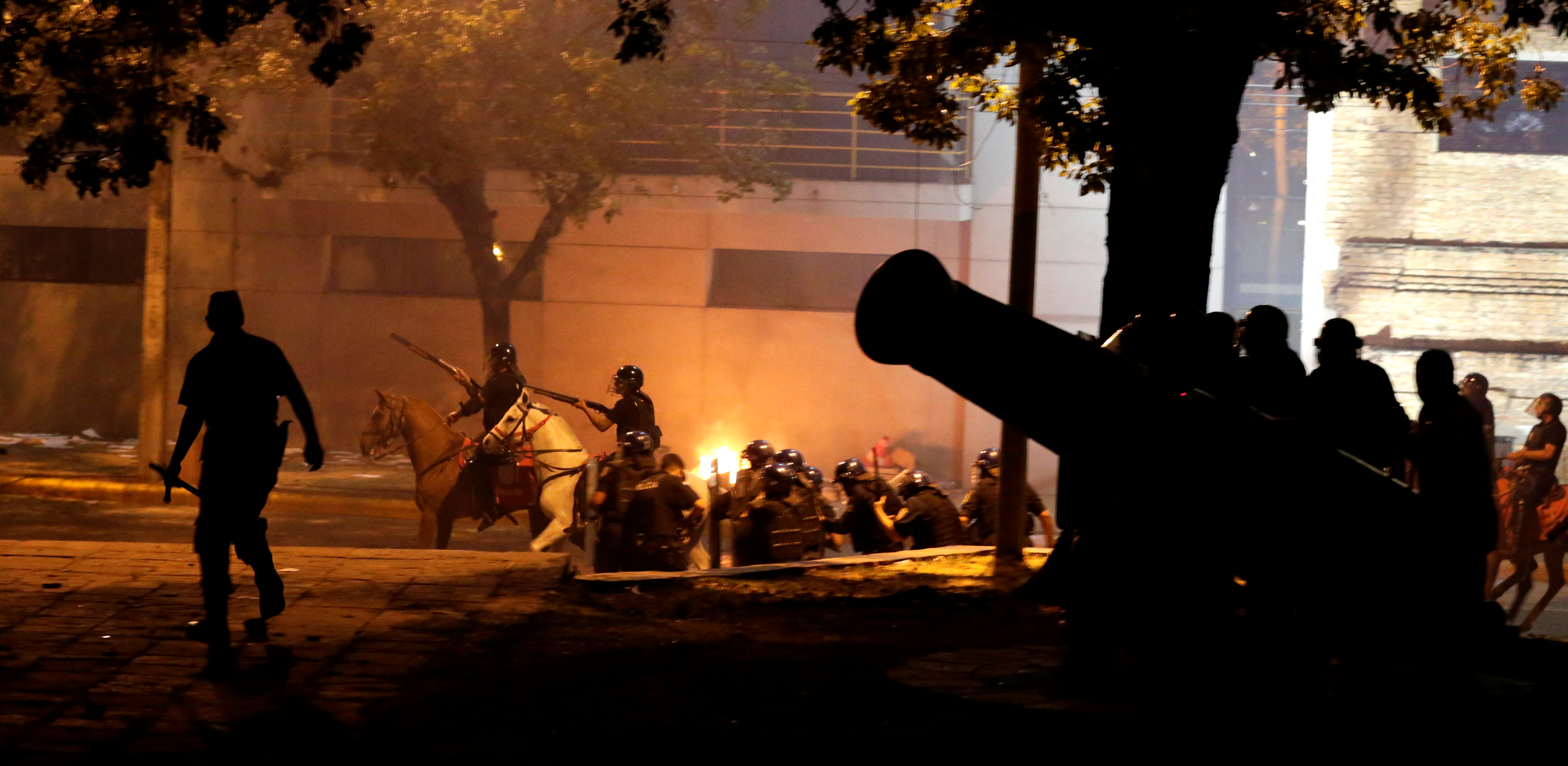Police on horseback ride past a statue of a cannon during a protest against a possible change in law to allow for presidential re-election in front of the Congress building in Asuncion