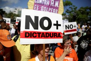 "An opposition supporter holds a placard that reads ""No more dictatorship"" as she takes part in a rally against Venezuela's President Nicolas Maduro's government in Caracas"