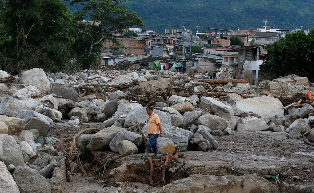 A man walks among the ruins after flooding and mudslides, caused by heavy rains leading several rivers to overflow, pushing sediment and rocks into buildings and roads, in Mocoa