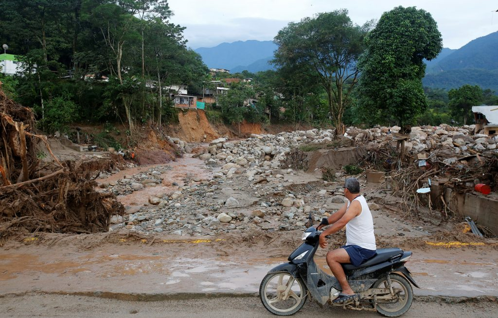 A man looks at a street destroyed after flooding and mudslides, caused by heavy rains leading several rivers to overflow, pushing sediment and rocks into buildings and roads, in Mocoa