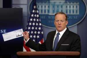 White House Press Secretary Sean Spicer shows a check from U.S. President Donald Trump's salary which will be donated to the National Park Service during a daily press briefing at the White House in D.C. Photo by Carlos Barria/Reuters