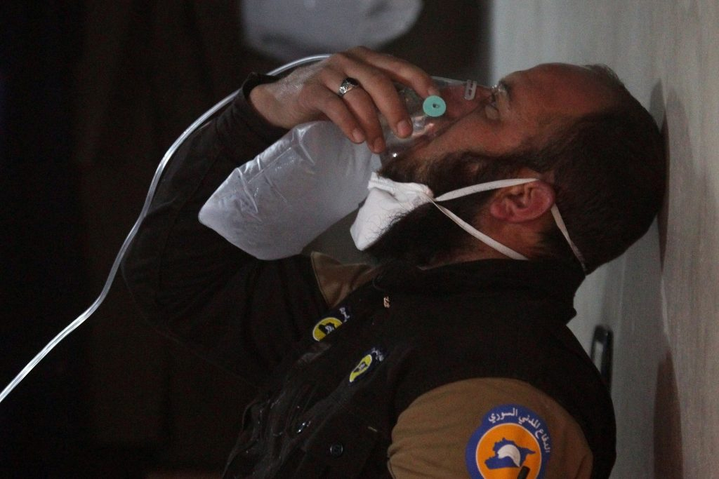 A rescue worker breathes through an oxygen mask. Photo by Ammar Abdullah/Reuters