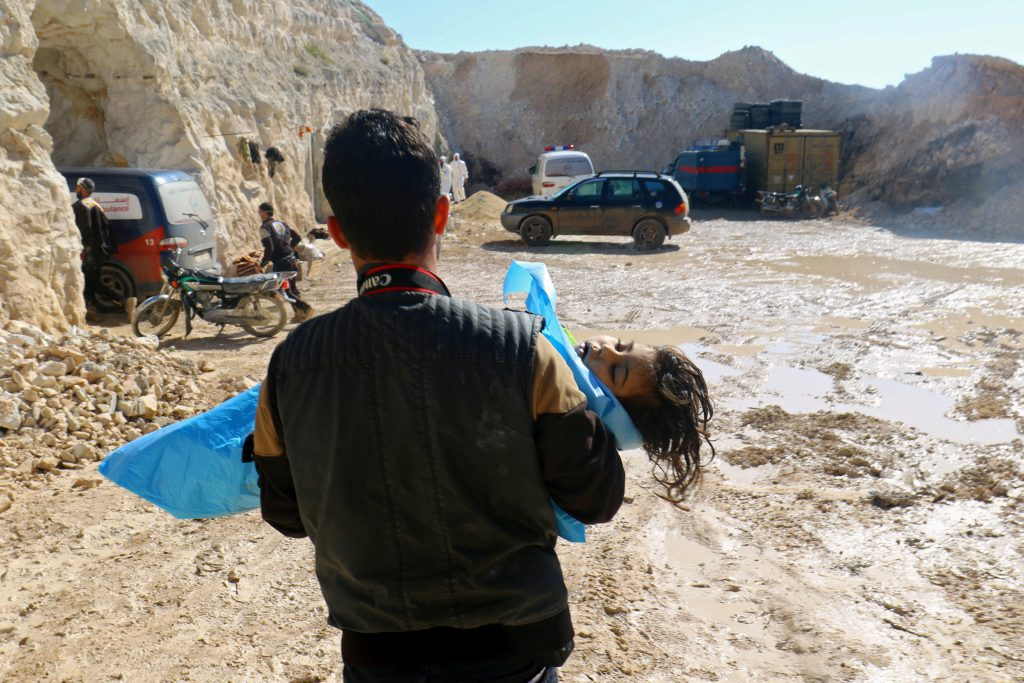 A man carries the body of a child away from the scene of airstrikes in Idlib in northern Syria on April 4. Photo by Ammar Abdullah/Reuters