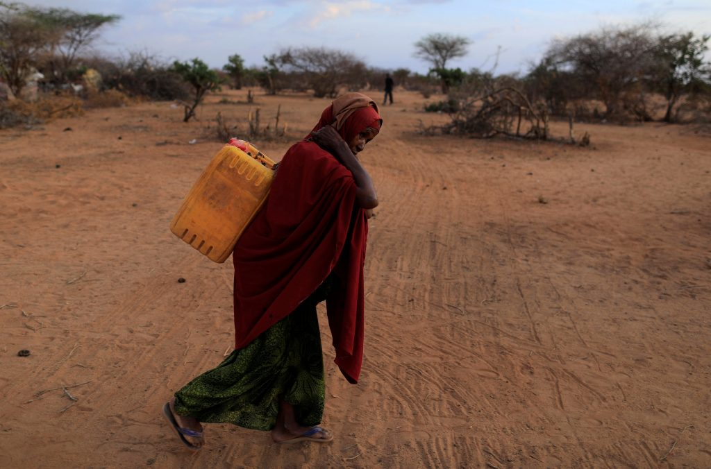 An internally displaced woman from a drought-hit area carries a jerrycan of water to her shelter in Dollow, Somalia, on the border with Ethiopia. Photo by Zohra Bensemra/Reuters