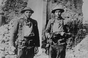 Two American soldiers, Cpl. Howard Thompson and James H. White, who were part of a group that killed and captured several Germans on March 7, 1918, pose with a pistol taken from a German soldier. Photo taken in Ancerviller, France, on March 11, 1918. Image courtesy of the Library of Congress/Handout via Reuters