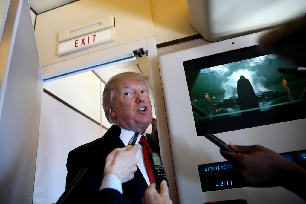 President Donald Trump talks to journalists, members of the travel pool, on April 6 on board of Air Force One during his trip to Palm Beach, Florida. Photo by REUTERS/Carlos Barria.