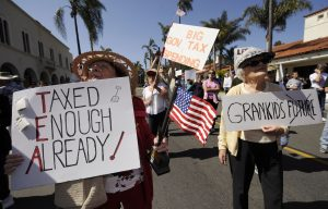 Anita Dwyer (L) and Bea Severson hold signs as they participate in a rally and march in protest of higher taxes in Santa Barbara, California in this file photo taken April 4, 2009. Taking inspiration from a landmark 1970s tax revolt, a determined group of activists say the moment is right for another voter uprising in California, where recession-battered residents have been hit with the highest income and sales tax rates in the nation. To match feature ECONOMY-CALIFORNIA/TAXES REUTERS/Phil McCarten/Files (UNITED STATES POLITICS BUSINESS CONFLICT) - RTXDRI1