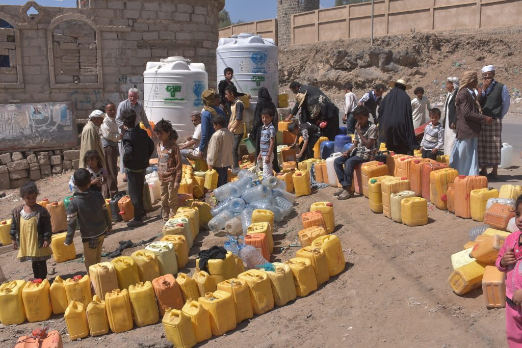 People line up to fill canisters with water from a tank provided by UNICEF in Sanaa, Yemen on March 5. Some 14.5 million people in Yemen have no access to safe drinking water. Photo by Algabal/UNICEF