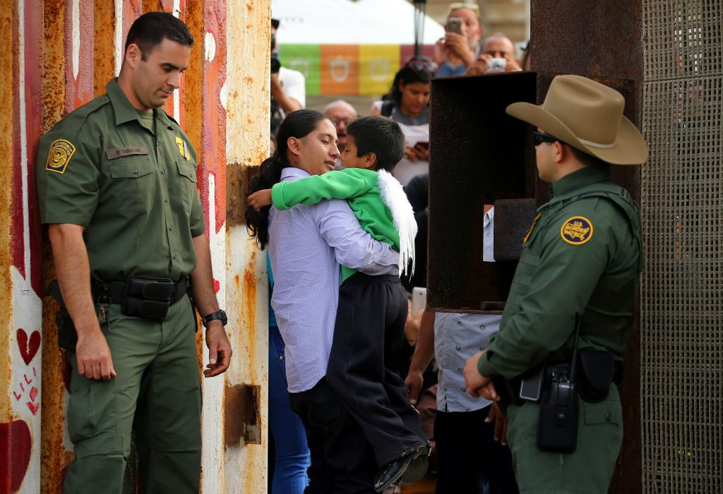U.S. Border patrol agents stand at an open gate on the fence along the Mexico border to allow Luis Eduardo Hernandez-Bautista to hug Ty'Jahnae Williams and his father Eduardo Hernandez (not in view) at the Border Field State Park, in California. Photo by REUTERS/Mike Blake.