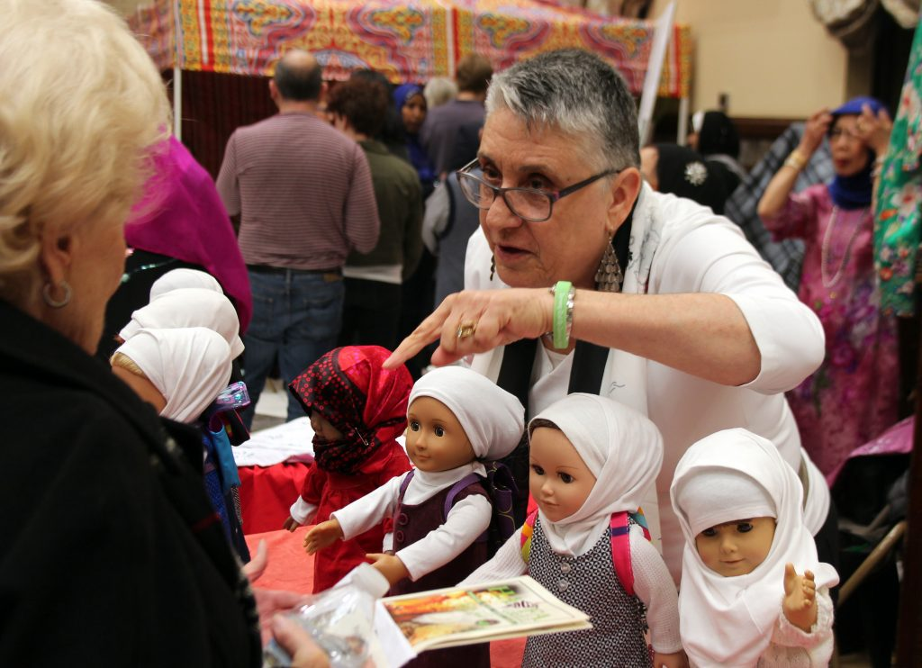 Refugee Doll Project founder Jeanne Trabulsi explains to a visitor at the Islamic Center open house how children can learn about refugee arrivals. Photo by Larisa Epatko/PBS NewsHour