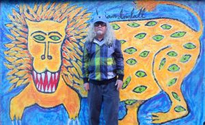Brian Dowdall, with one of his animal spirit paintings. Credit: American Visionary Art Museum