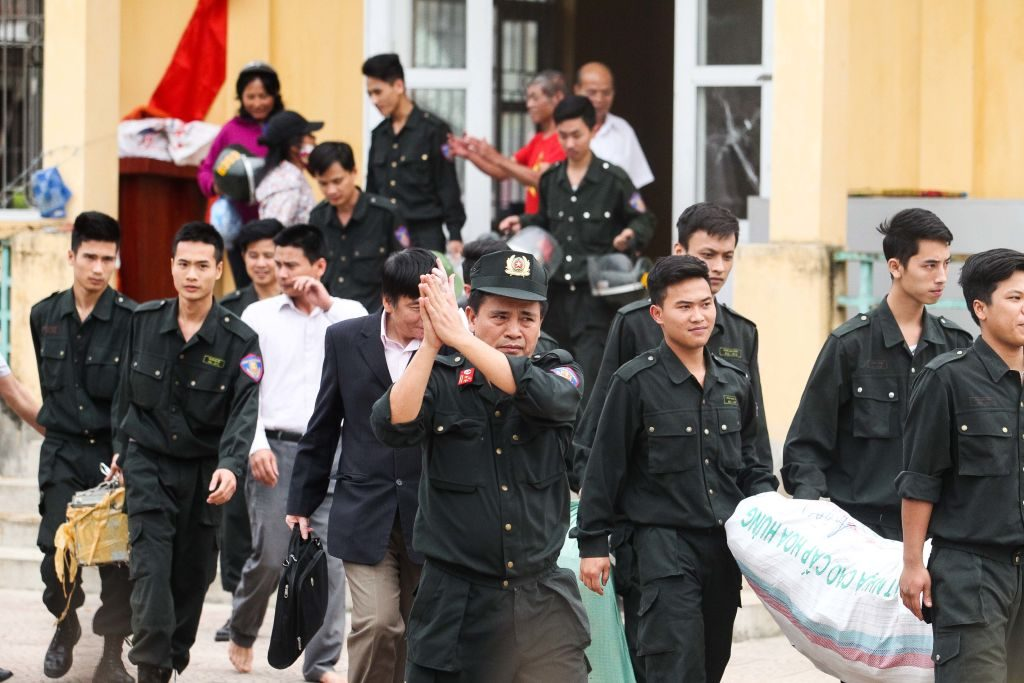Released policemen (wearing dark uniforms) walk out from the communal house at Dong Tam commune, My Duc district in Hanoi.  More than a dozen police and officials held hostage by Vietnamese villagers over a land dispute were released on April 22, state media reported, ending a week-long standoff that had gripped the country.  Photo by STR/AFP/Getty Images.