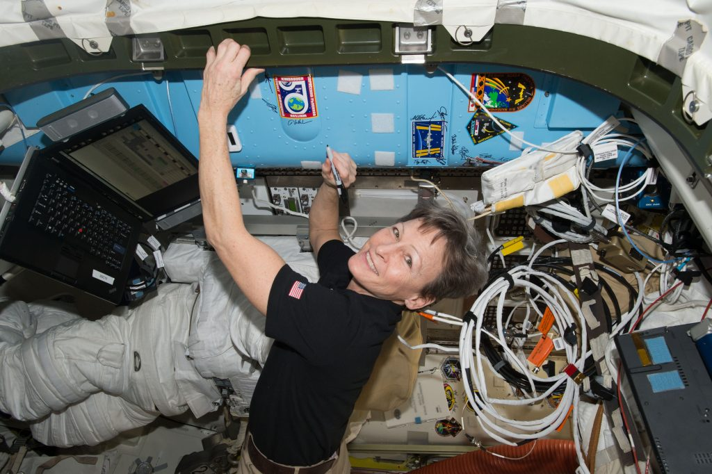 Astronaut Peggy Whitson signs a bulkhead on the International Space Station, as she breaks the U.S. record for cumulative time in space.