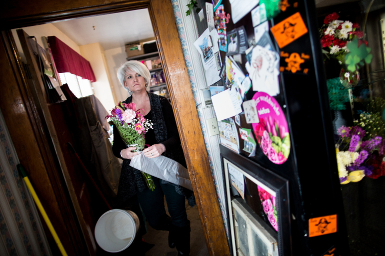 Tara Parsons, 42, prepares flowers for a customer. Parsons, who runs the Touch of Country Floral and Gifts shop in Arco, also serves as the town's coroner and volunteer EMT. Photo by M. Scott Mahaskey/Politico