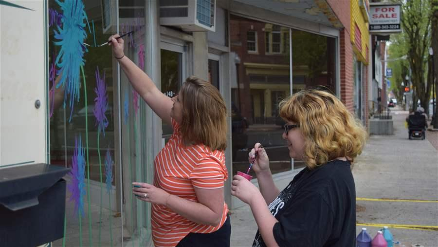 "Pocomoke High School teacher Brooke Gillespie and senior Rebeka Kline, who plans to study art at a local community college, decorate vacant storefronts in rural Pocomoke City, Maryland, as part of an after-school program to teach job skills. ""After they graduate, there isn't much here"" for young people looking for jobs, Gillespie said.© The Pew Charitable Trusts"