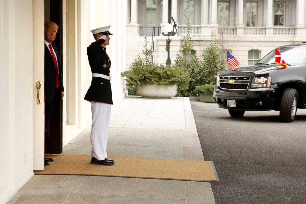President Donald Trump (L, in doorway) waits to welcome Denmark's Prime Minister Lars Lokke Rasmussen as his car arrives at the White House in Washington, D.C. Photo by REUTERS/Jonathan Ernst.