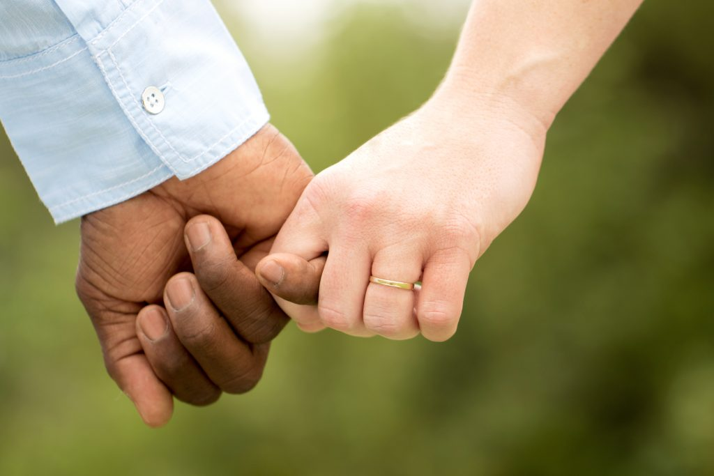 Love.  Rear view of a multiracial couple holding hand. Photo by Adobe Stock Images.