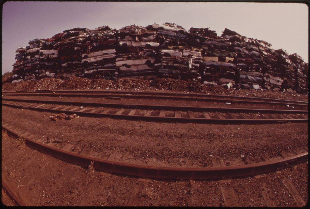 """North Philadelphia Junkyard Stacked With Cars For Scrap Metal, August 1973. Picture was taken as part of the <a href=""""https://www.flickr.com/photos/usnationalarchives/collections/72157620729903309/"""">EPA's DOCUMERICA Project</a>. Photo by Dick Swanson"""