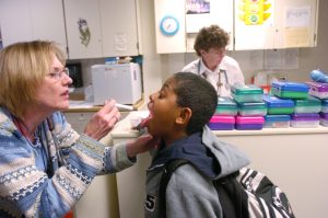 A nurse checks 9-year-old's throat while checking in for his daily medications and lung test at the Kunsberg School in Denver. Photo by Glenn Asakawa/The Denver Post via Getty Images