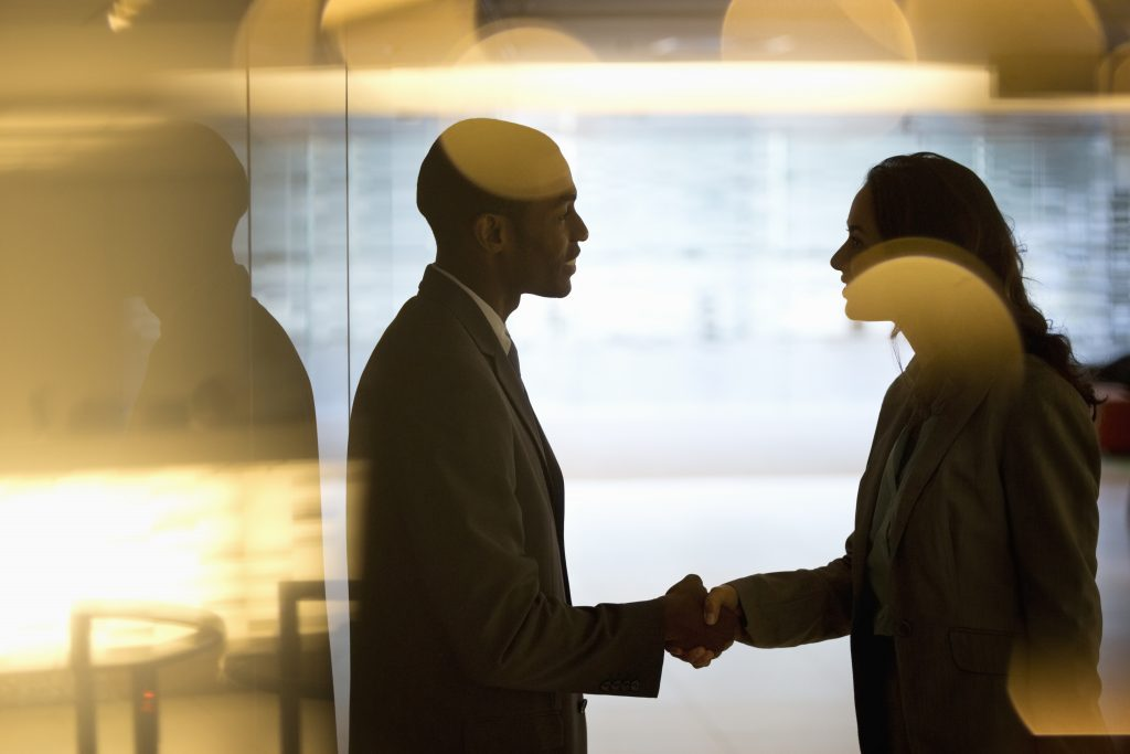 Businessman and businesswoman handshaking in lobby. Related words: business deal, job offer, handshake, interview. Photo by Tom Merton/Getty Images