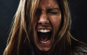 A young woman screaming uncontrollably while isolated on a black background. Photo by PeopleImages via Getty Images