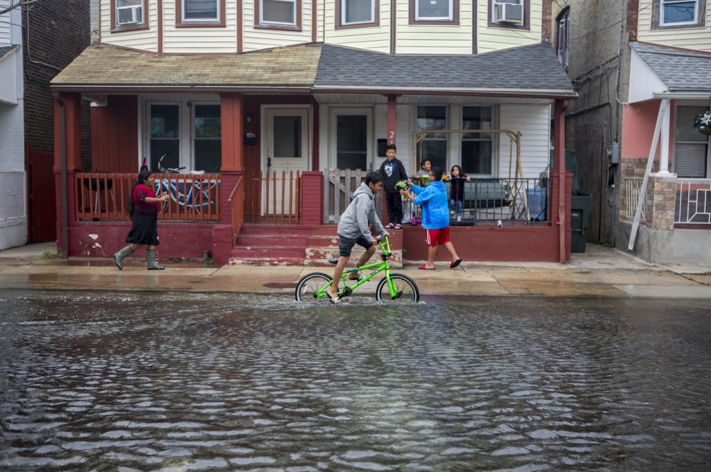 Kids play on a flooded Arizona Avenue on October 4, 2015 in Atlantic City, New Jersey. Some flooding and and power outages were reported all along the New Jersey shore this weekend due to converging storms.