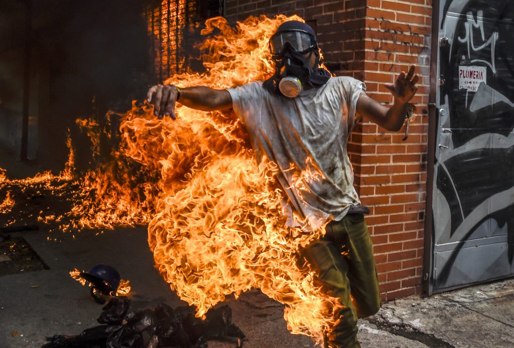 A demonstrator is burned after the gas tank of a police motorbike exploded during a protest against Venezuelan President Nicolas Maduro in Caracas on May 3. Photo by Juan Barreto/AFP/Getty Images
