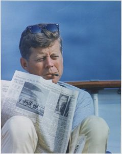 John F. Kennedy smokes a cigar and reads The New York Times on his boat off the coast of Hyannisport.  Photo by U.S. National Archives and Records Administration
