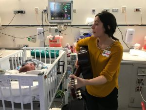 A music therapist plays guitar for babies admitted to the NICU. Photo by Terry Rubin