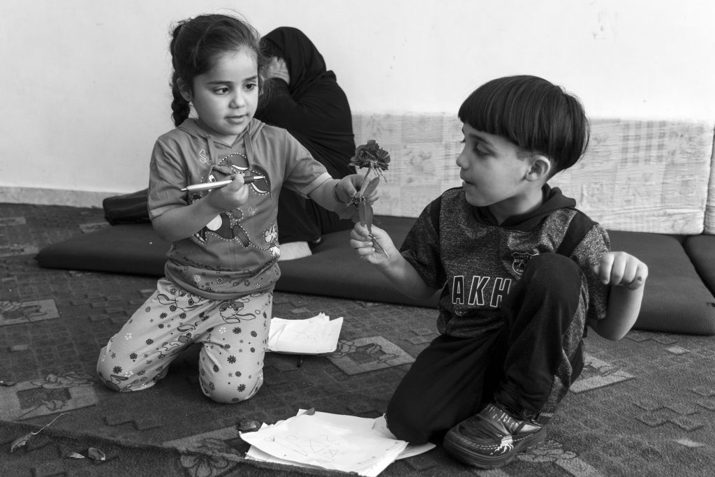 Doaa, 4, hands her big brother Mustafa, 5, a flower while playing at the Homs League in Amman Jordan. Photo by Sebastian Rich