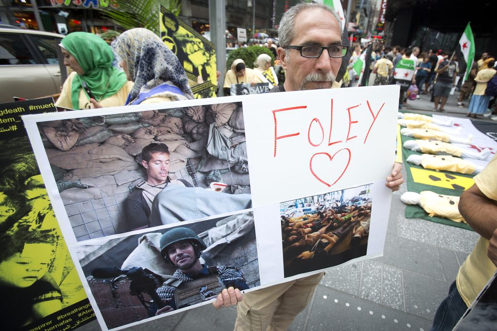 A man holds a sign in memory of American journalist James Foley during a protest against the Assad regime in Syria in Times Square in New York on Aug. 22, 2014. Photo by Carlo Allegri/Reuters