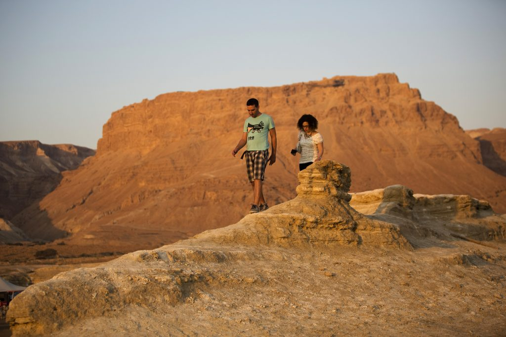 The Masada fortress is seen behind some hikers. President Donald Trump reportedly is planning to visit Masada, the site of Jewish resistance to Rome. President George W. Bush visited the historic fortress in 2008. Photo by Amir Cohen/Reuters