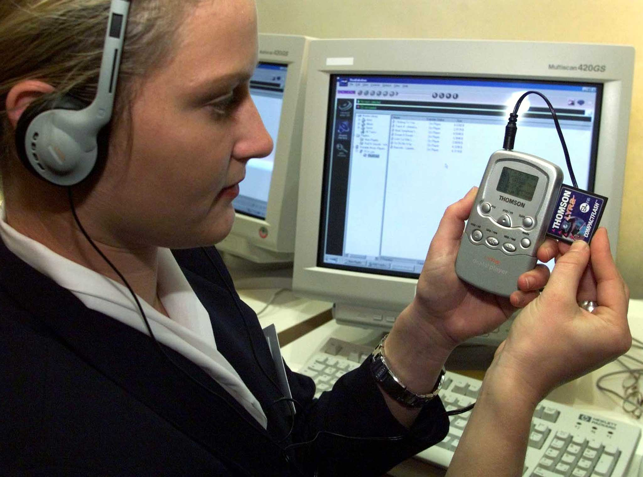 An employee listens to music with a Thomson Lyra MP3 music player. Picture taken in 1999. Photo by Reuters