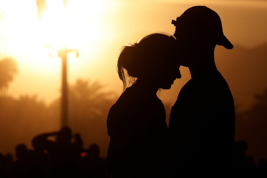 A couple embrace in the late afternoon sun during the Coachella Valley Music and Arts Festival in Indio, California, U.S. April 16, 2017. REUTERS/Carlo Allegri - RTS12KMY